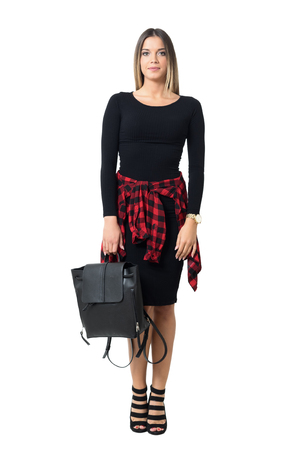 Stylish young woman wearing black dress carrying black leather bag looking at camera. Full body length isolated over white studio background.
