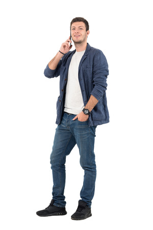 Happy smiling man in jeans and denim shirt talking on the phone looking at camera. Full body length portrait isolated over white background.