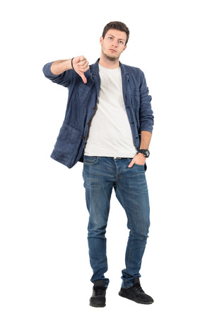 Disappointed young man in jeans showing thumbs down gesture at camera. Full body length portrait isolated over white background.
