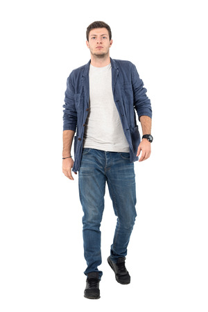 Young confident man in denim unbuttoned shirt and jeans walking towards camera. Full body length portrait isolated over white background.