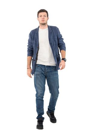 Joven confidente en denim desabrochado camisa y pantalones vaqueros caminando hacia la cámara. Retrato de longitud completa del cuerpo aislado sobre fondo blanco. Foto de archivo - 72732398