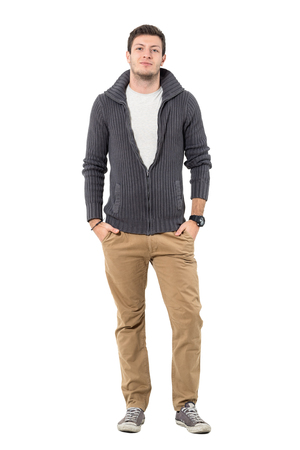 Young handsome casual man with unzipped sweater with hands in pockets. Full body length portrait isolated over white background.
