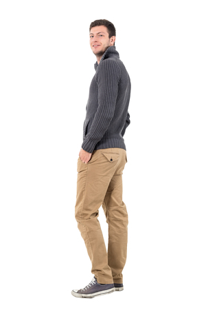 turn over: Rear view of young man in jumper with hands in pockets smiling at camera. Full body length portrait isolated over white background.