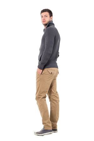 ochre: Side view of casual man in sweater walking away looking at camera over shoulder. Full body length portrait isolated over white background.