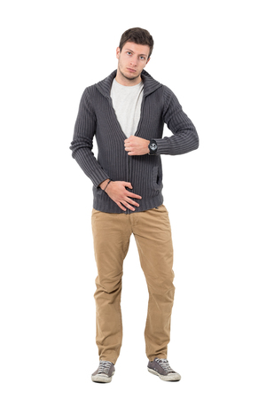 Casual man zipping jumper sweater looking at camera. Full body length portrait isolated over white background.