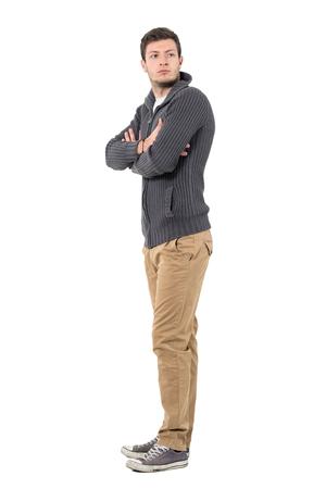 desconfianza: Vista lateral de joven casual con los brazos cruzados mirando hacia atrás sobre el hombro. Retrato de longitud completa del cuerpo aislado sobre fondo blanco.