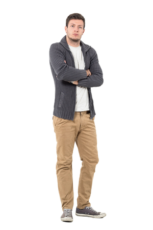 Serious young casual man in unzipped sweater with crossed arms looking at camera. Full body length portrait isolated over white background. Stock Photo