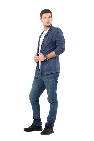 casual men: Young male fashion model in denim shirt and jeans looking back over shoulder holding collar. Full body length portrait isolated over white background.