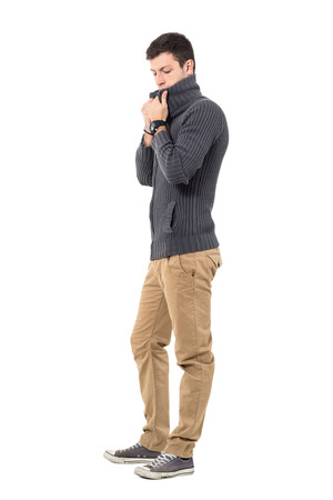 Young casual man in sweater adjusting collar looking down. Side view. Full body length portrait isolated over white background. Stock Photo