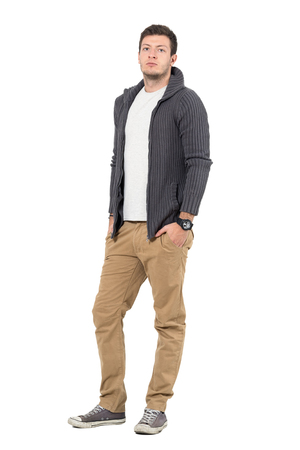 Handsome confident young man in ocher pants and gray sweater looking at camera. Full body length portrait isolated over white background.