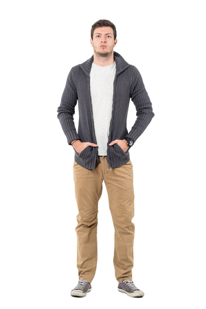 Serious young casual man wearing sneakers and sweater with hands in pockets. Full body length portrait isolated over white background.