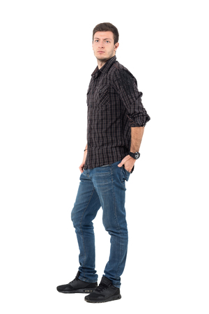 Side view of handsome male model in casual wear with hand in back pocket. Full body length portrait isolated over white background.