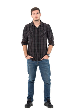 Defensive young man tilting head looking at camera with hands in pockets. Full body length portrait isolated over white background.