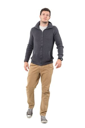 Young confident casual man wearing zip sweater walking towards camera. Full body length portrait isolated over white background.