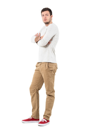 Side view of young confident stylish man with crossed arms. Full body length portrait isolated over white background.