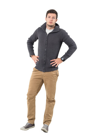 Confident young handsome casual man wearing zipper sweater with hands on hips. Full body length portrait isolated over white background.
