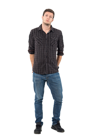 Handsome man with rolled up sleeves with hands in back pockets. Full body length portrait isolated over white background.