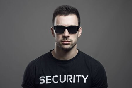 Ernstig humeurig portret van veiligheidsagent die zonnebril dragen die camera over donkere grijze studioachtergrond bekijken. Stockfoto