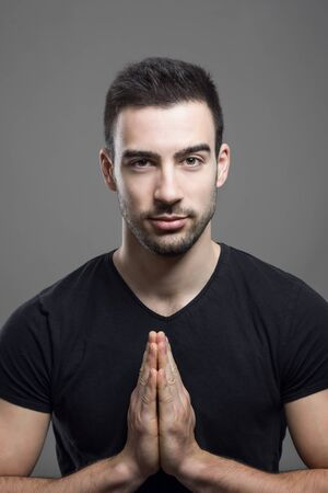 man with beard: Young fitness male model touching hand palms namaste gesture. over dark gray studio background. Stock Photo