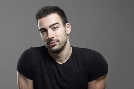 ojos marrones: hombre guapo amigable pensativo con la cabeza inclinada mirando a la cámara sobre fondo oscuro gris del estudio.