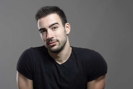 Pensive friendly handsome man with head cocked looking at camera over dark gray studio background. Stock Photo