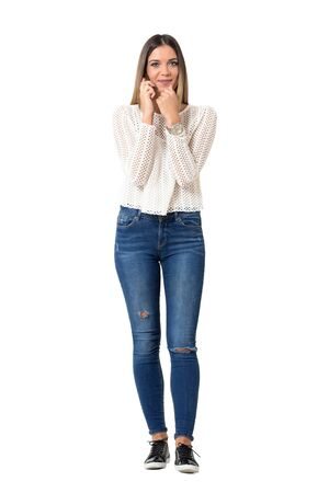 Pretty casual woman in jeans and braided shirt talking on the cellphone. Full body length portrait isolated over white background.