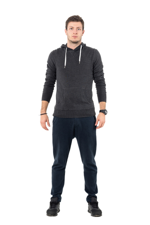 Confident willing young athletic man in sportswear looking at camera. Full body length portrait over white studio background. Stock Photo