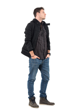 Side view of young man in autumn clothes with hands in pockets looking away. Full body length portrait over white studio background.