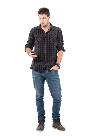 white person: Cool relaxed young casual man typing message on mobile phone.  Full body length portrait over white studio background.