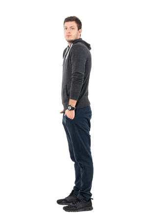 Side view of standing young man in sportswear with hands in pockets looking at camera. Full body length portrait over white studio background. Stock Photo