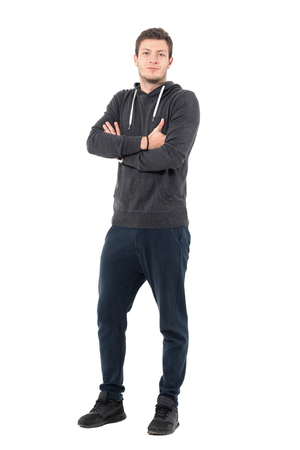 Smiling young casual man in sportswear with crossed hands looking at camera. Full body length portrait over white studio background.