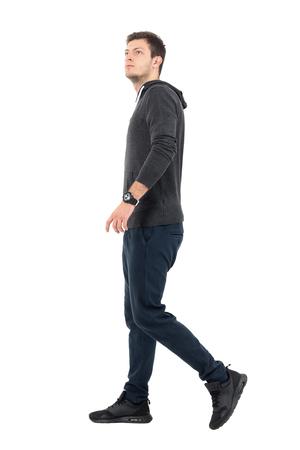 Zijaanzicht van de jonge knappe sportieve mens in sweatshirt en zweetbroek lopen die omhoog eruit zien. Het volledige portret van de lichaamslengte over witte studioachtergrond.