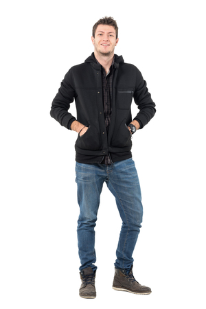 Happy young relaxed smiling man with hands in hooded jacket pockets looking at camera. Full body length portrait over white studio background.