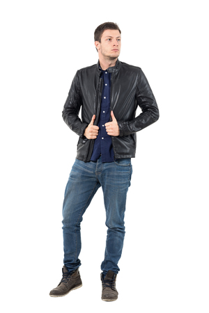 attitudes: Confident young man pulling leather jacket collar looking away. Full body length portrait isolated over white studio background.