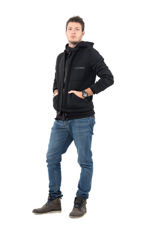 Serious confident male model in black hooded jacket with hands in pockets. Full body length portrait over white studio background. Фото со стока