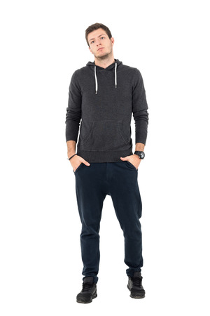 Confident serious man wearing comfortable sportswear looking at camera with hands in pockets. Full body length portrait over white studio background.