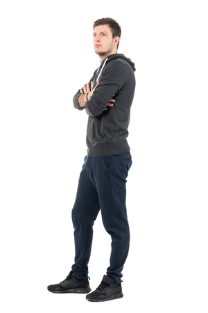 Side view of young man in hooded sweatshirt and tracksuit with crossed arms looking up. Full body length portrait over white studio background.
