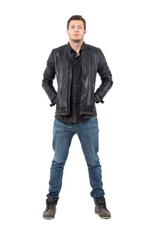 Front of young man in jeans and jacket with hands in pockets looking at camera. Full body length portrait isolated over white studio background. Stock Photo