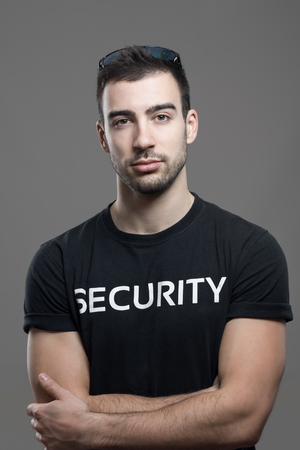 face guard: Cool fit security guard in black shirt with crossed arms looking at camera. Atmospheric contrasty portrait over gray studio background.