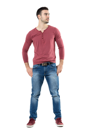 Relaxed young happy stylish man wearing v-neck shirt with hands on hips looking away.  Full body length portrait isolated over white background.