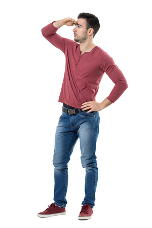Young casual style man looking at distance covering and shading eyes from sunlight with hand.  Full body length isolated over white background.