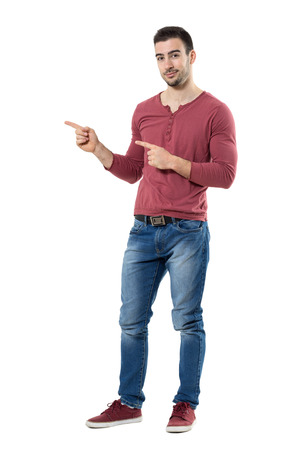 Happy young friendly man presenter pointing finger showing copyspace looking at camera.  Full body length portrait isolated over white background.