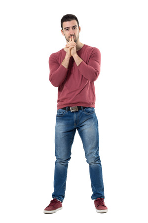 Thinking young stylish man with finger over mouth looking at camera.  Full body length portrait isolated over white background. Stock Photo