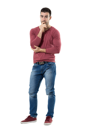 suspiciously: Worried young casual man with hands on chin looking at camera suspiciously.  Full body length portrait isolated over white background. Stock Photo