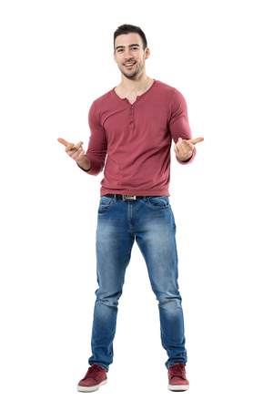 Cheerful trendy casual man smiling and pointing at camera choosing you.  Full body length portrait isolated over white background. Stock Photo