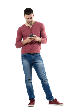 Young stylish casual man using mobile phone looking down at phone.  Full body length portrait isolated over white background. Stock Photo