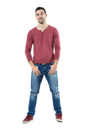 Cool funny stylish smiling casual man with raised eyebrows looking at camera.  Full body length portrait isolated over white background.