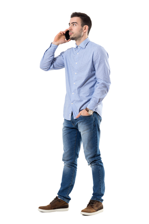Successful young businessman talking on the phone looking away. Full body length portrait isolated over white background.