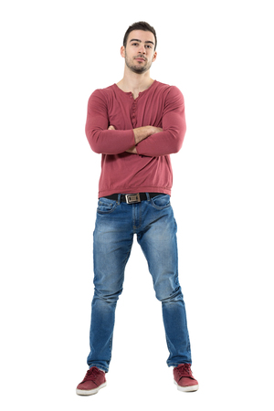 Cool relaxed casual man with crossed arms and titled head looking at camera.  Full body length portrait isolated over white background. Stock Photo