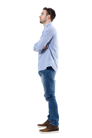 Side view of young businessman with crossed arms looking away. Full body length portrait isolated over white background. Stock Photo